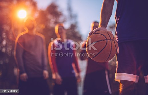 Basketball player holding ball at outdoor court
