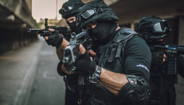 SWAT always ready for action Group of men, special forces armed team standing on the street, ready for action. counter terrorism stock pictures, royalty-free photos & images