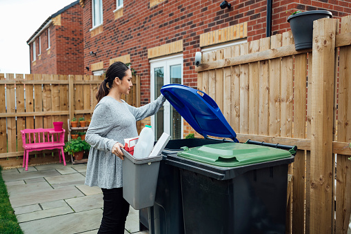 Pregnant woman disposing of her household recycling into an outdoor bin in her garden. She is in the North East of England.