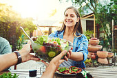 Shot of young woman taking a salad bowl from a friend while sitting around a table outdoors