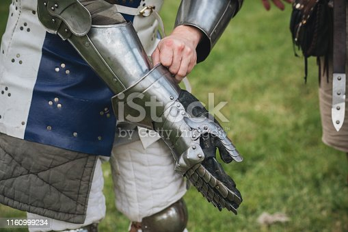 Man putting on protective gear on a medieval festival
