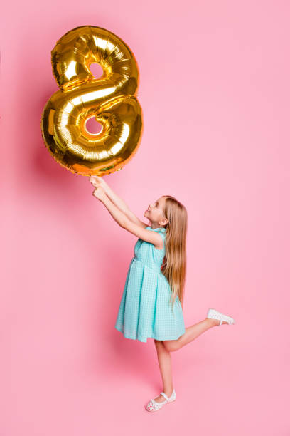 I am 8 years old! Vertical full-length side profile view portrait of cute lovely beautiful girl celebrating birthday, she is holding golden balloon in shape of figure-eight isolated on pink background stock photo