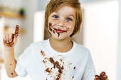 Portrait of a cute little boy with chocolate stains looking at camera.