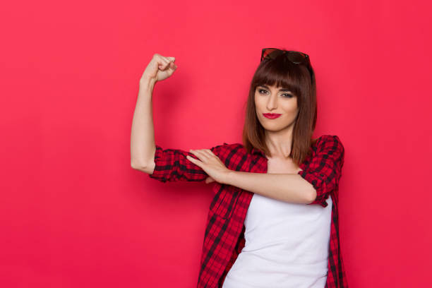 I Am A Strong Woman Young woman in unbuttoned red lumberjack shirt is flexing arm and looking at camera. Waist up studio shot on red background. flexing muscles stock pictures, royalty-free photos & images