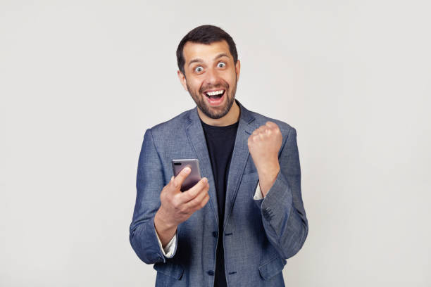I am a winner Happy business man holding a smartphone and celebrating his victory and success is very excited, encouraging emotions stock photo
