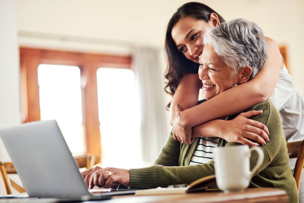 I am always so proud of you Cropped shot of an attractive young woman hugging her grandmother before helping her with her finances on a laptop lifestyles stock pictures, royalty-free photos & images
