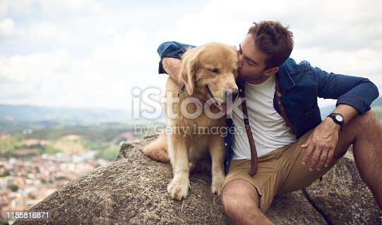 Cropped shot of a handsome young man sitting on a rock with his golden retriever after a day out hiking