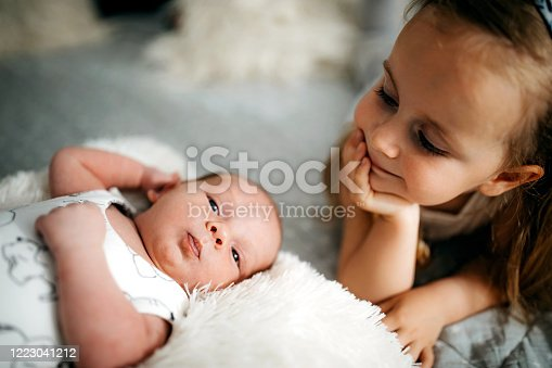 Young girl embracing her baby brother in bed