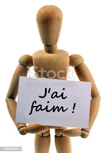 mannequin en bois tenant une carte sur laquelle est écrit j'ai faim