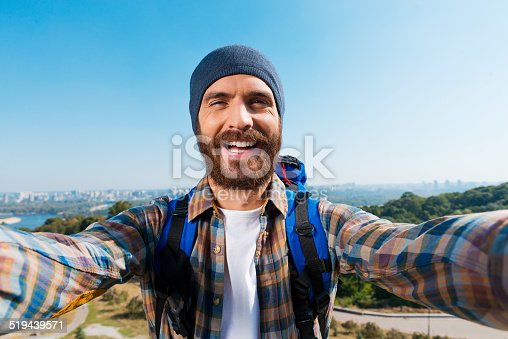 Handsome young man carrying backpack and taking a picture of himself