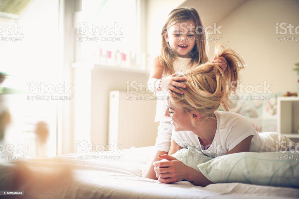 I am moms hairdresser. Little girl. stock photo