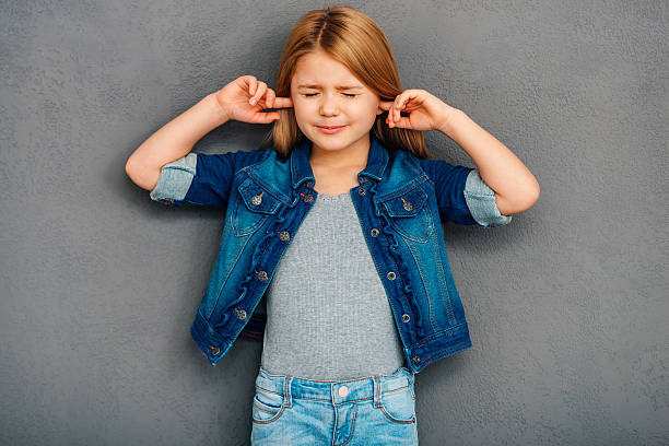 I am not listening! Beautiful littlegirl covering ears with hands and keeping eyes closedwhile standing against grey background hands covering ears stock pictures, royalty-free photos & images