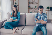 istock I am not talking to you! Mistrust and cheat problems. Annoyed couple is ignoring each other, sitting on the couch indoors at home with sad faces 937826400