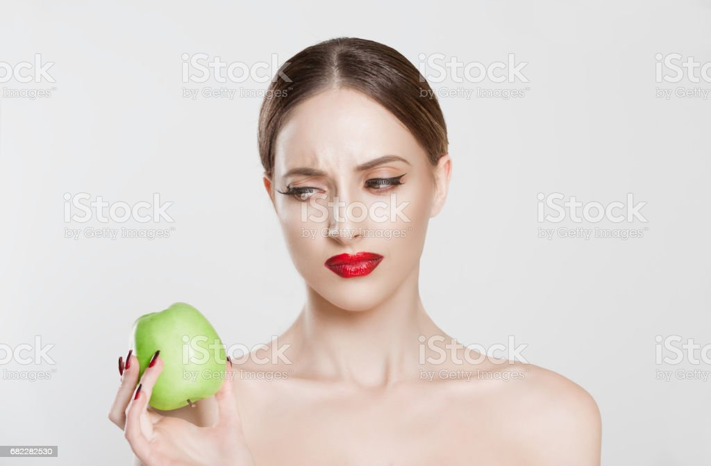 I am sick of this diet! Displeased young girl looking with disgust disliking apple isolated white background, fresh fruit diet dislike concept, negative disgusted emotion on face stock photo