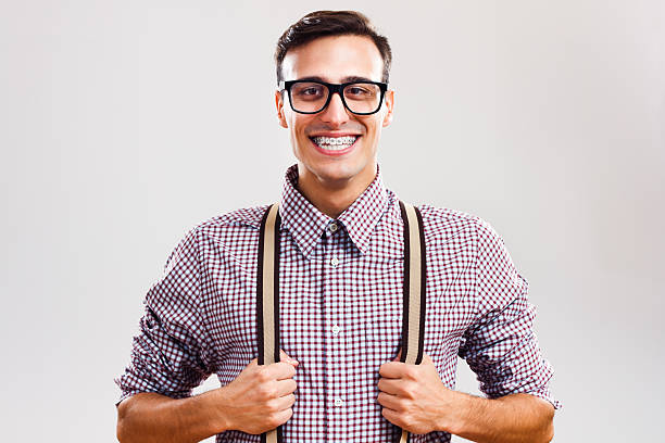 I am so handsome! Portrait of funny handsome nerd guy pulling his suspenders. suspenders stock pictures, royalty-free photos & images