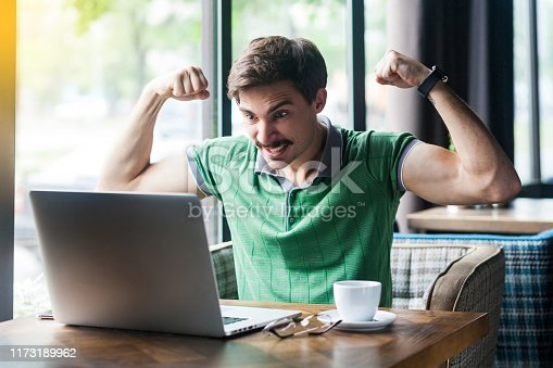 I am strong! Young aggressive businessman in green t-shirt sitting, looking at laptop screen on video call, showing his biceps muscle, angry face. business concept. indoor shot near window at daytime.