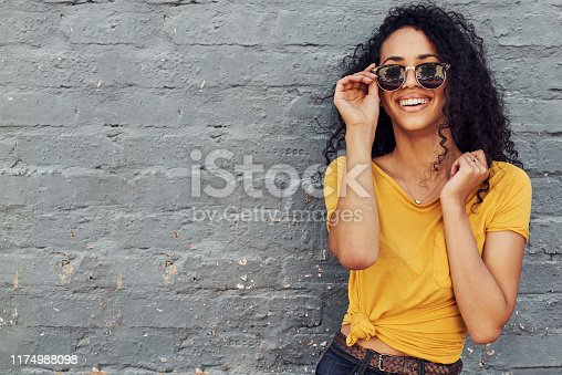 Cropped portrait of an attractive young woman wearing sunglasses and smiling while standing against a gray background outdoors