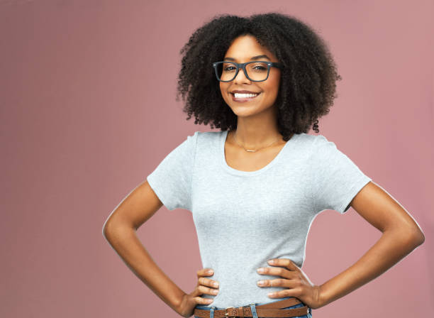 I am who I am and proud of it Studio shot of an attractive and confident young woman posing against a pink background akimbo stock pictures, royalty-free photos & images