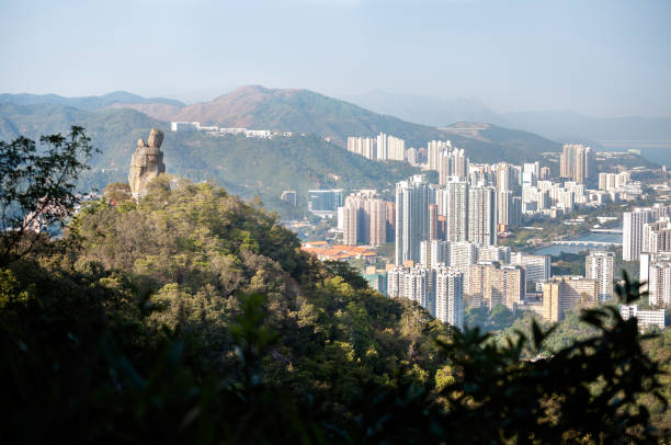 Amah Rock, with Shatin new town in the background, at Lion Rock Country Park, Hong Kong LION ROCK COUNTRY PARK, HONG KONG - FEB 2, 2012 - Amah Rock, with Shatin new town in the background, at Lion Rock Country Park, Hong Kong sha tin stock pictures, royalty-free photos & images