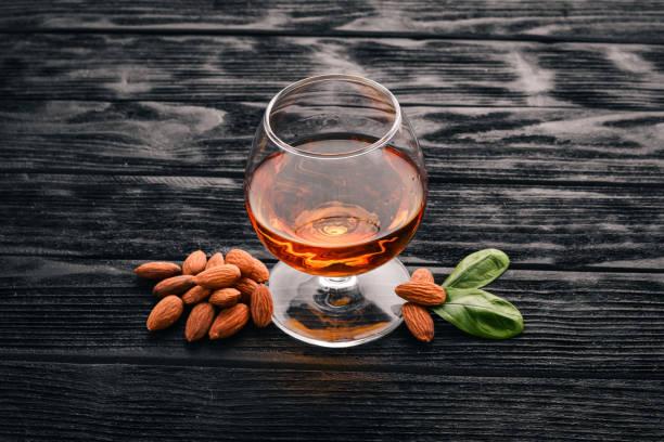 Amaretto licor de amêndoa. Amêndoa em um fundo de madeira. Vista superior da bebida italiana. Espaço livre para texto. - foto de acervo