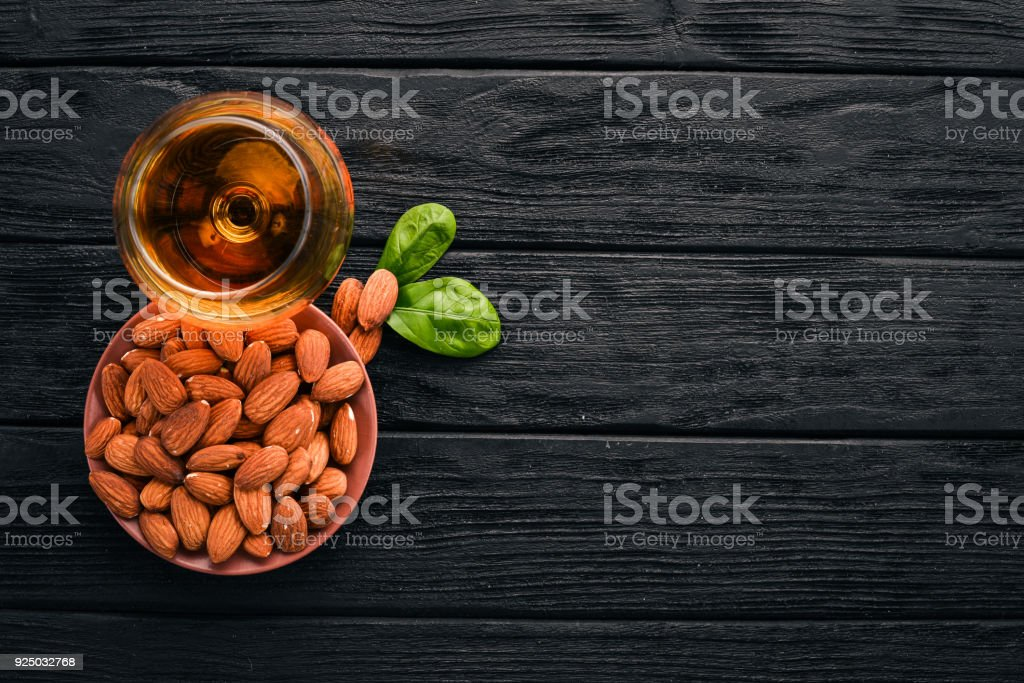 Amaretto Almond Liquor. Almond On a wooden background. Italian drink Top view. Free space for text. stock photo