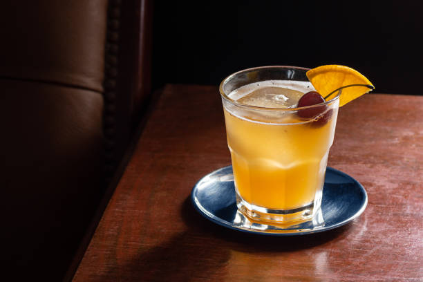 amaretto sour cocktail on the rocks with cherry and orange garnish in dark luxurious bar - kwaśny smak zdjęcia i obrazy z banku zdjęć