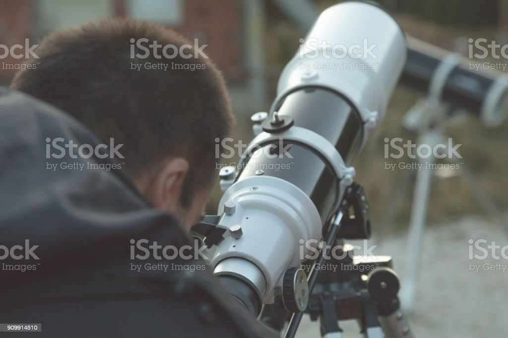 Amateur astronomer looking through a telescope outdoors. stock photo