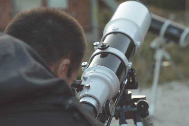 astronome amateur, regardant à travers un télescope à l'extérieur. - astronomie photos et images de collection