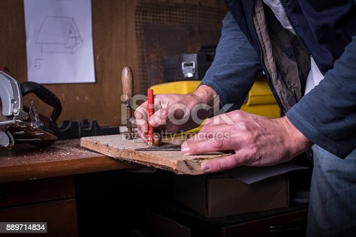 Amateur carpenter marking a line with a protractor on plank
