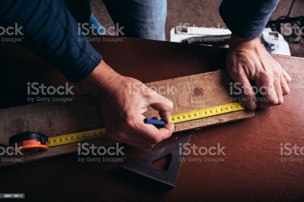 Amateur carpenter measures the board with the meter tape stock photo