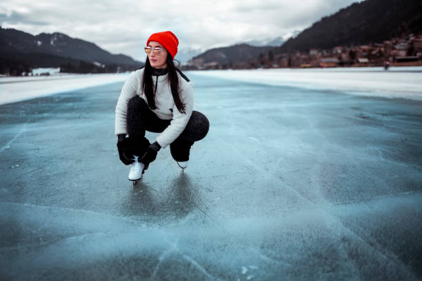 amateur ice skater tying her skate laces while on the ice outside - skate liberdade gorro imagens e fotografias de stock