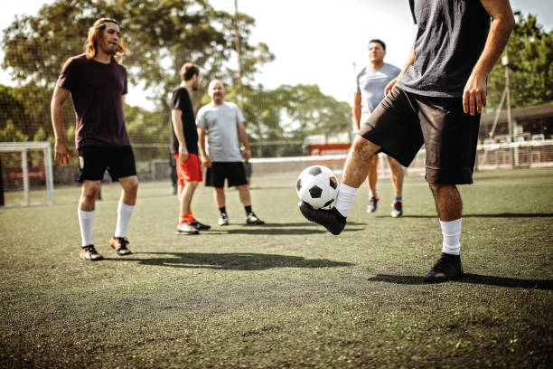 Amateur male soccer team playing soccer outdoor stock photo