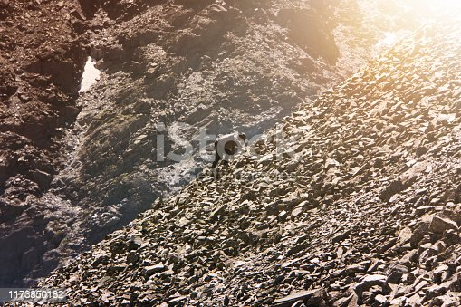 Amateur mountaineering. Man climbing up hill to reach the peak of the mountain. guy climbs up the rocks. Persistence, determination, strength, reaching the target concepts. stone alluvium