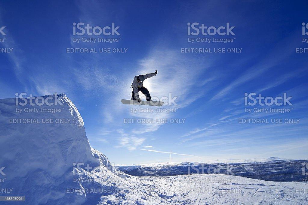 Amateur snowboarder making a grab in big air jump. stock photo