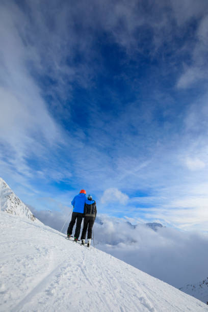 Amateur Winter Sports alpine skiing. Friends woman and man snow skier skiing at sunny ski resort. High mountain snowy landscape.  Alps mountain Europe, Italy. stock photo