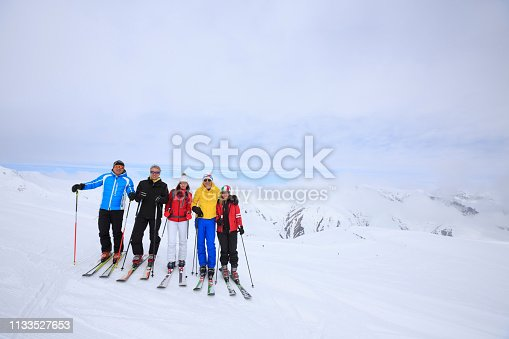Amateur Winter Sports  alpine skiing. Group of skiers. Best friends men and women, snow skiers, enjoying  skiing.  High mountain snowy landscape. Livigno mountain range, Alps. It is located in the Italiy.