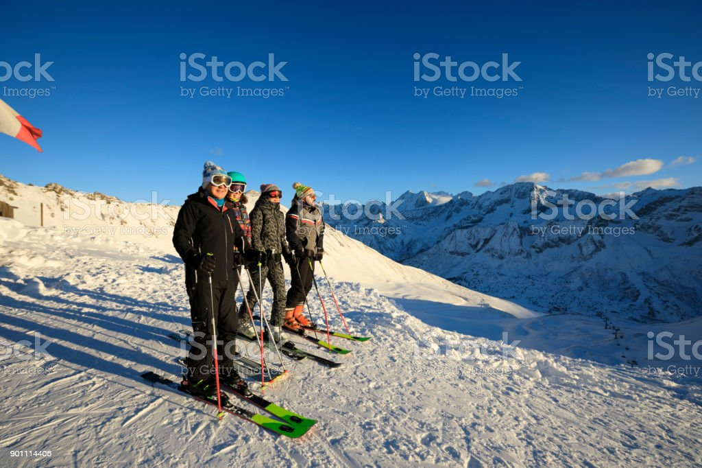Amateur Winter Sports alpine skiing. Group of skiers. Best friends men and  women, snow skiers enjoying on sunny ski resorts. High mountain snowy  landscape.