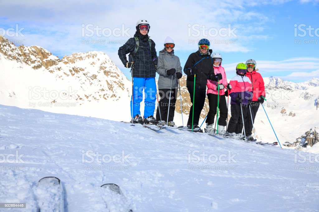 Amateur Winter Sports alpine skiing. Group of skiers, family mother and  father with children, snow skiers enjoying on sunny ski resorts.