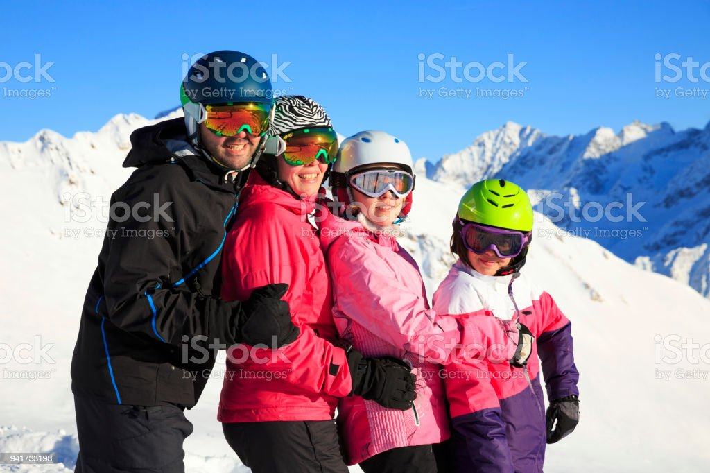 Amateur Winter Sports alpine skiing. Group of skiers, family mother and father with children, snow skiers enjoying on sunny ski resorts. High mountain snowy landscape. Italian Alps mountain of the Dolomites Italy, Europe. stock photo