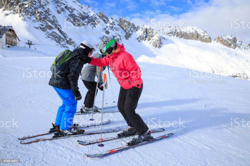 Amateur Winter Sports alpine skiing. Group of skiers, family mother with children, snow skiers enjoying on sunny ski resorts. High mountain snowy landscape. Italian Alps mountain of the Dolomites Italy, Europe. stock photo