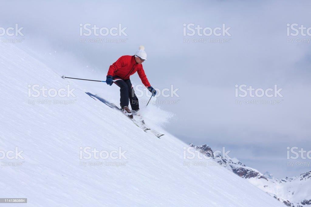 Amateur Winter Sports alpine skiing. Man snow skier skiing at sunny...