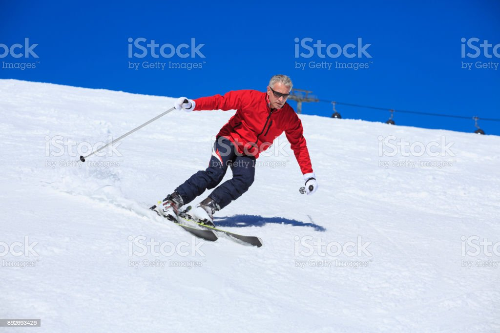 Amateur Winter Sports alpine skiing. Man snow skier skiing at sunny...