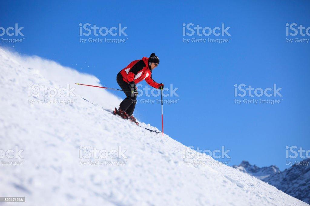 Amateur Winter Sports  alpine skiing. Men , snow skiers, enjoying on sunny ski resorts.  High mountain snowy landscape. Dolomite mountain range, Alps. It is located in the Italiy. stock photo