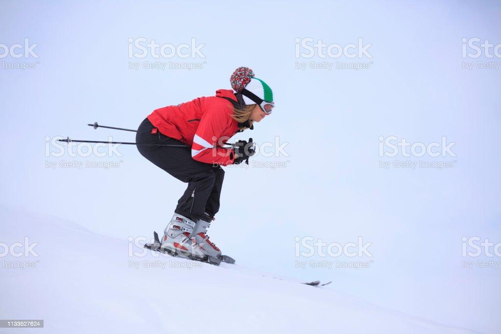 Amateur Winter Sports alpine skiing. Woman snow skier skiing at ski...