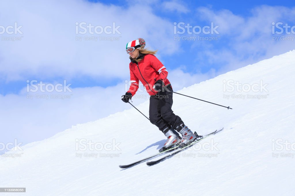 Amateur Winter Sports alpine skiing. Woman snow skier skiing at sunny...