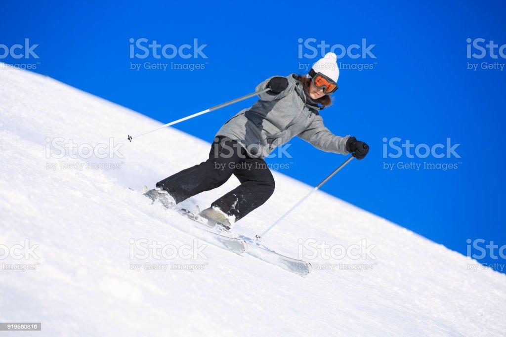 Amateur Winter Sports Girl skier skiing at sunny ski resort Dolomites...