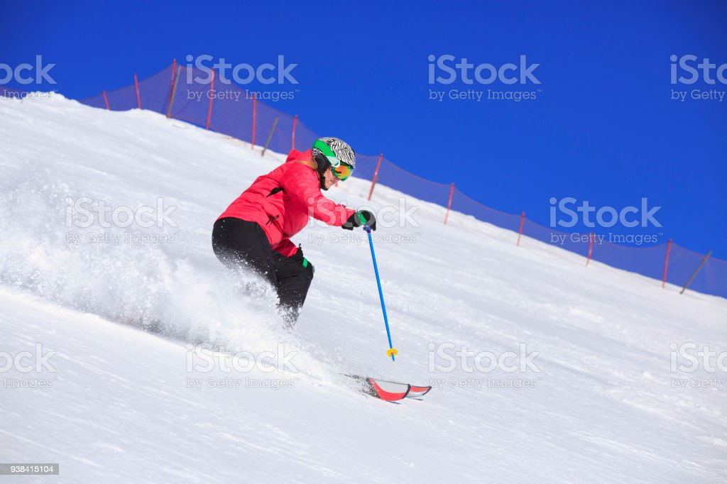 Amateur Winter Sports woman skier skiing at sunny ski resort...