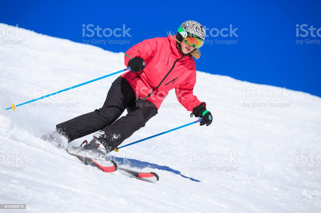 Amateur Winter Sports woman skier skiing at sunny ski resort...