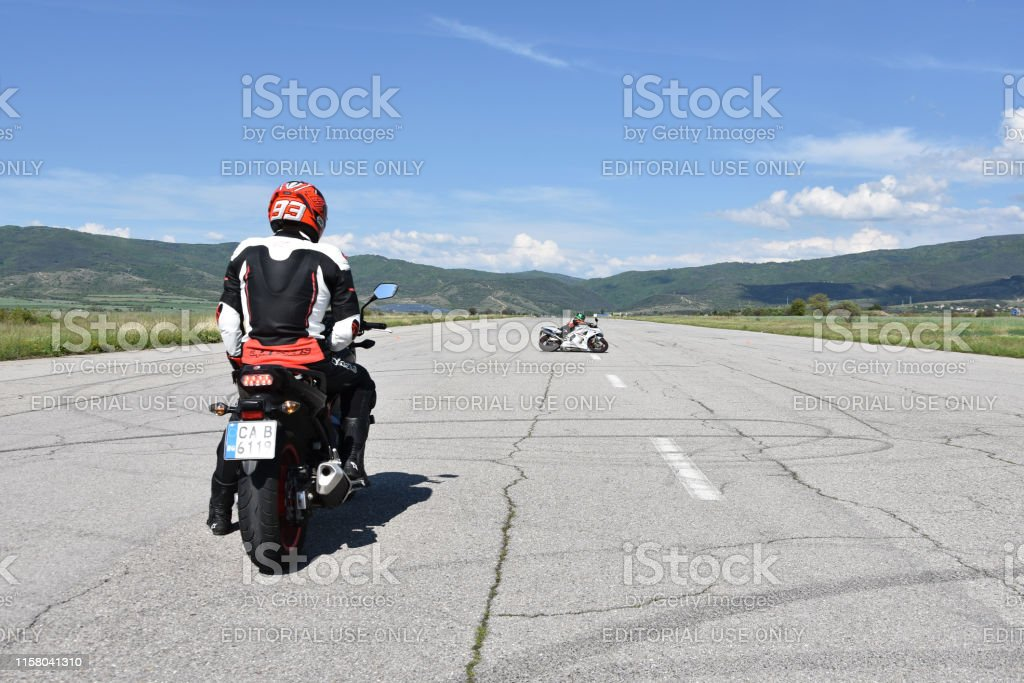 Young man on a motorcycle watching his fellow motorcyclist drifting...