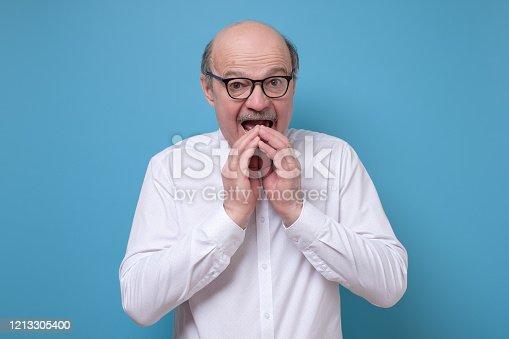 661896674 istock photo Amazed afraid senior man is shocked with news having stupor. 1213305400